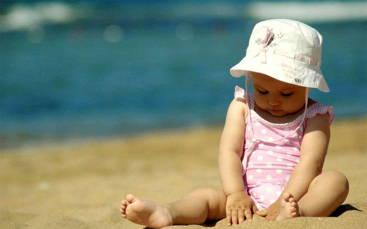 ребенок сидит на песке